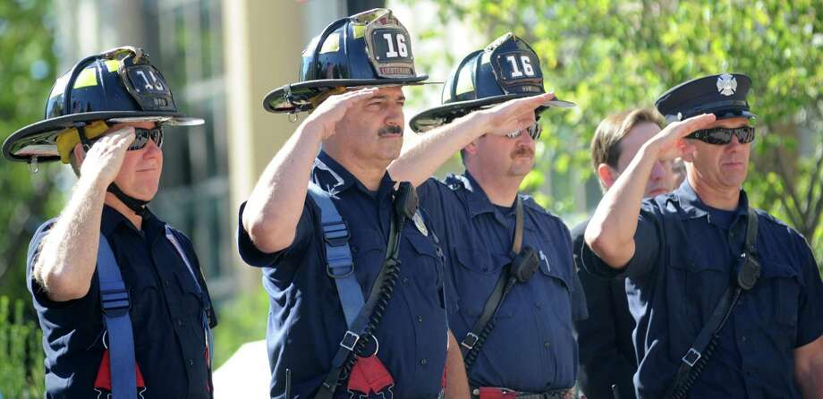 Firefighters salute at a Tuesday, Sept. 11, 2012, ceremony marking the 11th anniversary of the terrorist attacks on Sept. 11, 2001 with a brief speaking program at the Margaret E. Morton Government Center in Bridgeport, Conn. Photo: Cathy Zuraw / Connecticut Post