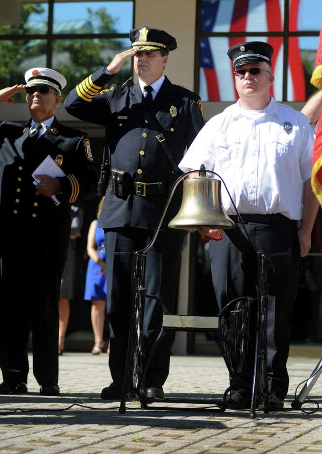 Police Chief Joseph L. Gaudett salutes as Lt. Joe Pelaggi rings the fire bell at a ceremony to mark the 11th anniversary of the terrorist attacks on Sept. 11, 2001 with a brief speaking program at the Margaret E. Morton Government Center in Bridgeport, Conn. on Tuesday, Sept. 11, 2012. Photo: Cathy Zuraw / Connecticut Post