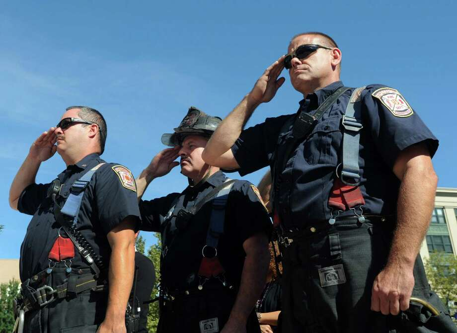 Lt. Kenny Domschine, firefighters Will Terron and firefighter Jim Bonosconi salute at a Tuesday, Sept. 11, 2012, ceremony marking the 11th anniversary of the terrorist attacks on Sept. 11, 2001 with a brief speaking program at the Margaret E. Morton Government Center in Bridgeport, Conn. Photo: Cathy Zuraw / Connecticut Post