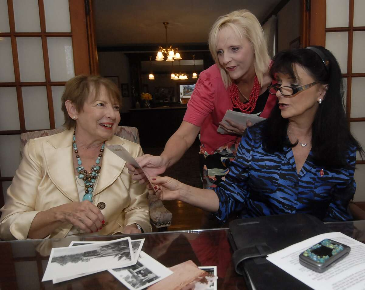 Lynn Cardiff, first executive director of the Katy Area Chamber of Commerce; Cassie Richter, volunteer and Texas West Oaks Hospital employee; and Carol Adams, Katy City Council member, sort photos for the group's 50th anniversary.