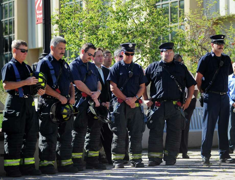 Firefighters bow their heads at a Tuesday, Sept. 11, 2012, ceremony marking the 11th anniversary of the terrorist attacks on Sept. 11, 2001 with a brief speaking program at the Margaret E. Morton Government Center in Bridgeport, Conn. Photo: Cathy Zuraw / Connecticut Post