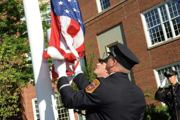 Norwalk fire department inspector Kirk McDonald, left, and Fire Department Lt. Scott Rywolt raise the American flag at the 9/11 Remembrance Ceremony at Norwalk City Hall on Tuesday, Sept. 11, 2012. Photo: Helen Neafsey / Greenwich Time