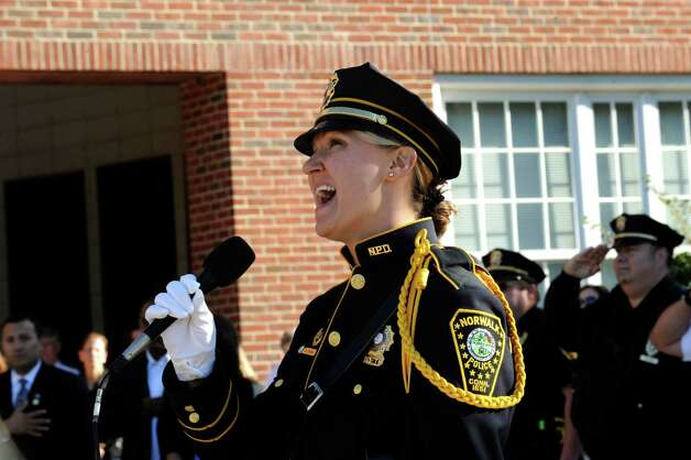 Norwalk Police Detective Kristine Lapak sings the National Anthem at the 9/11 Remembrance Ceremony at Norwalk City Hall Tuesday on Sept. 11, 2012. Photo: Helen Neafsey / Greenwich Time