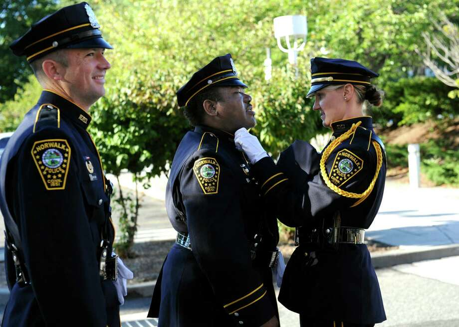 Norwalk Police Officer Gabriel Demott watches while Norwalk Police Officer Carl Williams and Norwalk Police detective  Kristine Lapak get ready for the 9/11 Remembrance Ceremony at Norwalk City Hall on Tuesday, Sept. 11, 2012. Photo: Helen Neafsey / Greenwich Time