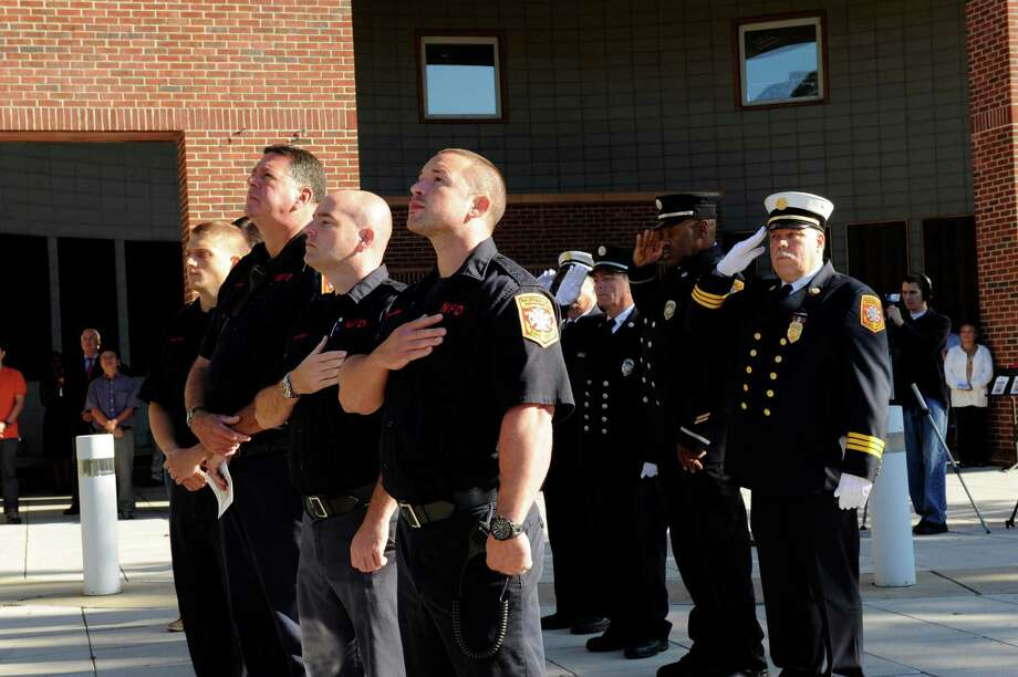 Members representing all the Norwalk fire/rescue personnel salute the flag at the 9/11 Remembrance Ceremony at Norwalk City Hall on Tuesday, Sept. 11, 2012. Photo: Helen Neafsey / Greenwich Time