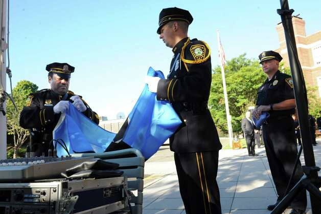 Norwalk Police Officers Carl Williams, left, and Gabriel Demott raise a 9/11 flag while Chief of Police Thomas Kulhawick looks on at the 9/11 Remembrance Ceremony at Norwalk City Hall Tuesday, Sept. 11, 2012. Photo: Helen Neafsey / Greenwich Time