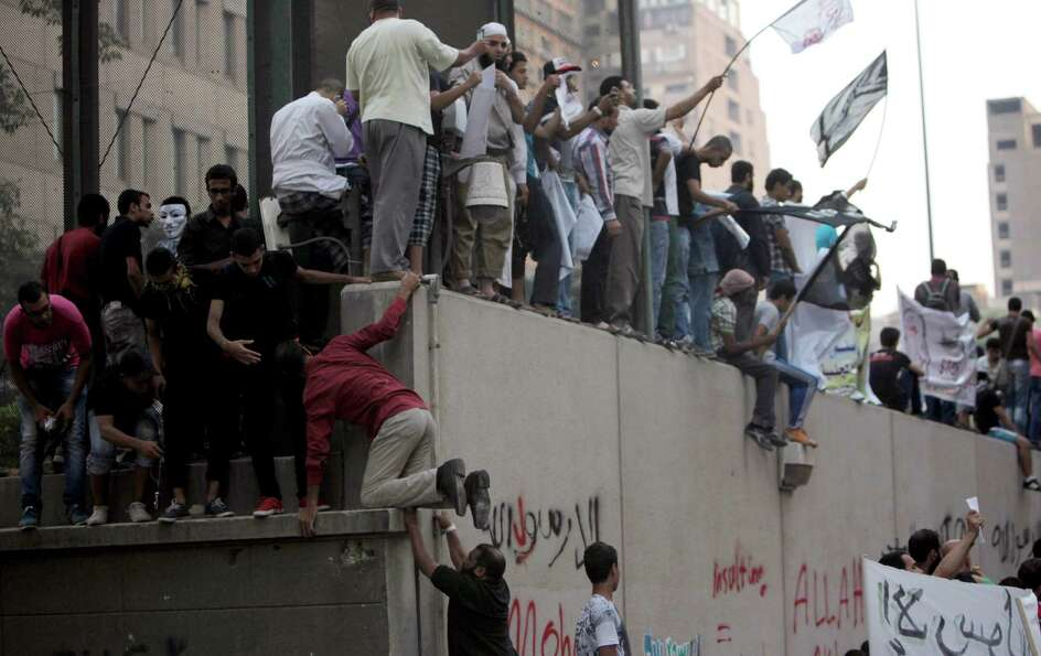 Egyptian protesters climb the walls of the U.S. embassy with Arabic graffiti that reads