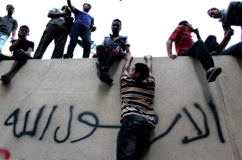 "Egyptian protesters climb the walls of the U.S. embassy with Arabic graffiti that reads ""any one but you God's prophet"" during a protest in Cairo on Tuesday. Egyptian protesters, largely ultra conservative Islamists, have climbed the walls of the U.S. embassy in Cairo, went into the courtyard and brought down the flag, replacing it with a black flag with Islamic inscription, in protest of a film deemed offensive of Islam. (AP Photo/Nasser Nasser) Photo: Ap/getty"