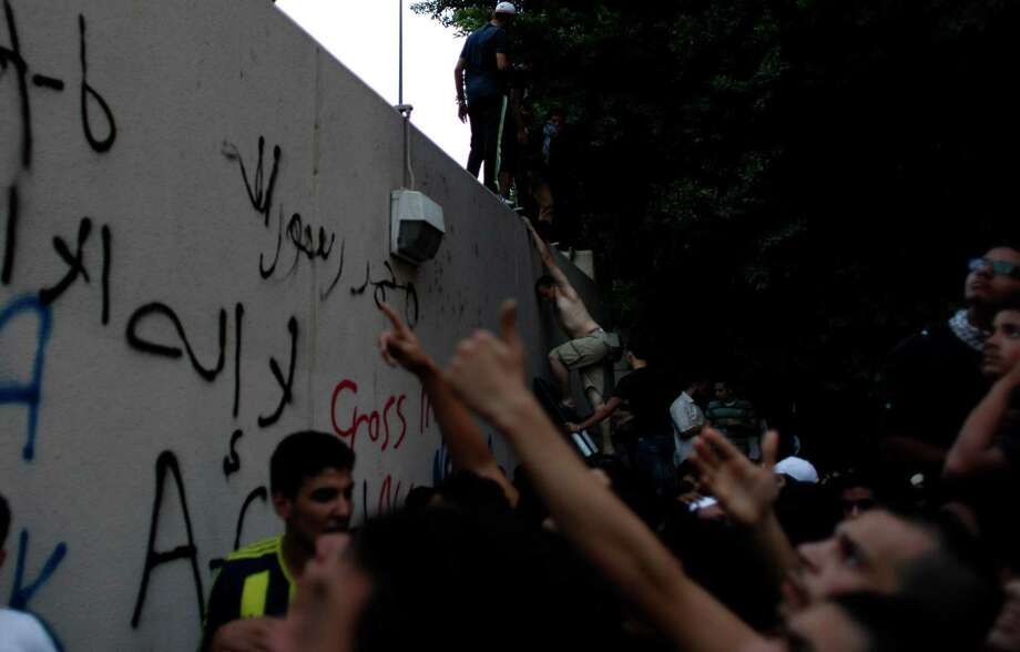 An Egyptian protester climbs the walls of the U.S. embassy during protests in Cairo on Tuesday. Egyptian protesters, largely ultra conservative Islamists, have climbed the walls of the U.S. embassy in Cairo, went into the courtyard and brought down the flag, replacing it with a black flag with Islamic inscription, in protest of a film deemed offensive of Islam. (AP Photo/Nasser Nasser) Photo: Ap/getty