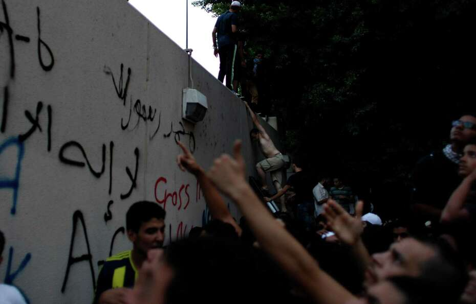 An Egyptian protester climbs the walls of the U.S. embassy during protests in Cairo on Tuesday. Egyp
