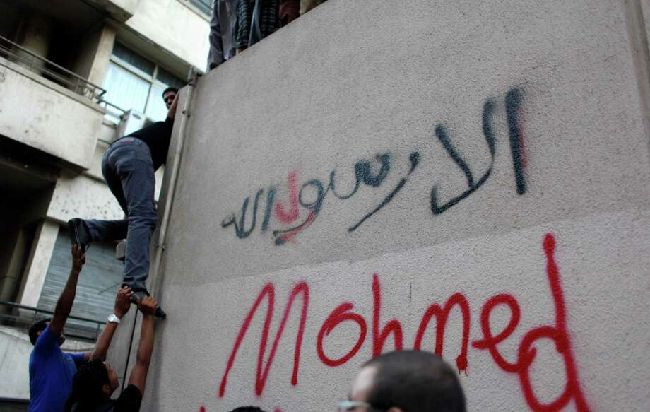 "Egyptian protesters climb the walls of the U.S. embassy with Arabic graffiti that reads ""any one but you God's prophet"" during protests in Cairo on Tuesday. Egyptian protesters, largely ultra conservative Islamists, have climbed the walls of the U.S. embassy in Cairo, went into the courtyard and brought down the flag, replacing it with a black flag with Islamic inscription, in protest of a film deemed offensive of Islam. (AP Photo/Nasser Nasser) Photo: Ap/getty"