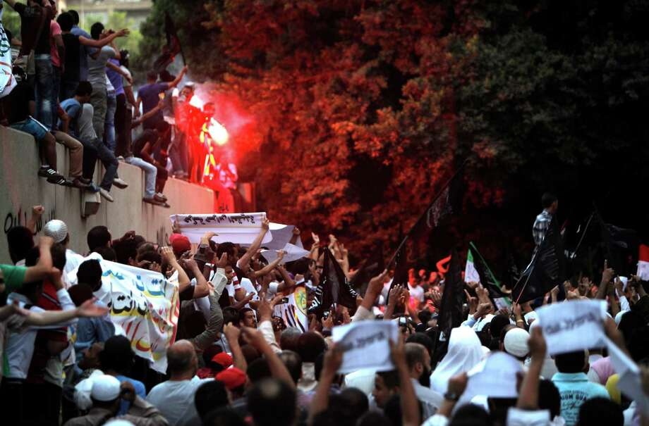 Egyptian protesters climb the walls of the U.S. embassy during protests in Cairo on Tuesday. Egyptian protesters, largely ultra conservative Islamists, have climbed the walls of the U.S. embassy in Cairo, went into the courtyard and brought down the flag, replacing it with a black flag with Islamic inscription, in protest of a film deemed offensive of Islam. (AP Photo/Nasser Nasser) Photo: Ap/getty