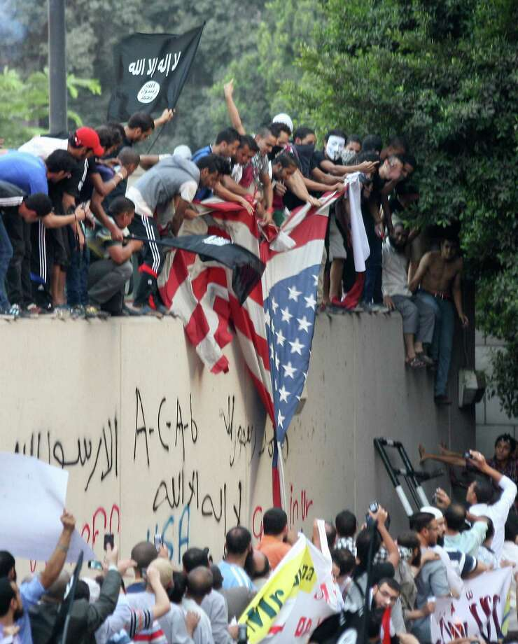 Protesters destroy an American flag pulled down from the U.S. embassy in Cairo on Tuesday Egyptian protesters, largely ultra conservative Islamists, have climbed the walls of the U.S. embassy in Cairo, went into the courtyard and brought down the flag, replacing it with a black flag with Islamic inscription, in protest of a film deemed offensive of Islam. (AP Photo/Mohammed Abu Zaid) Photo: Ap/getty
