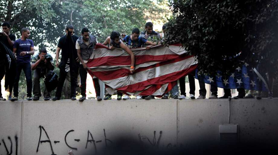 Egyptian protesters standing on the sidewall of the U.S. embassy move down an American flag pulled down from the embassy in Cairo on Tuesday Egyptian protesters, largely ultra conservative Islamists, have climbed the walls of the U.S. embassy in Cairo, went into the courtyard and brought down the flag, replacing it with a black flag with Islamic inscription, in protest of a film deemed offensive of Islam. (AP Photo/Nasser Nasser) Photo: Ap/getty