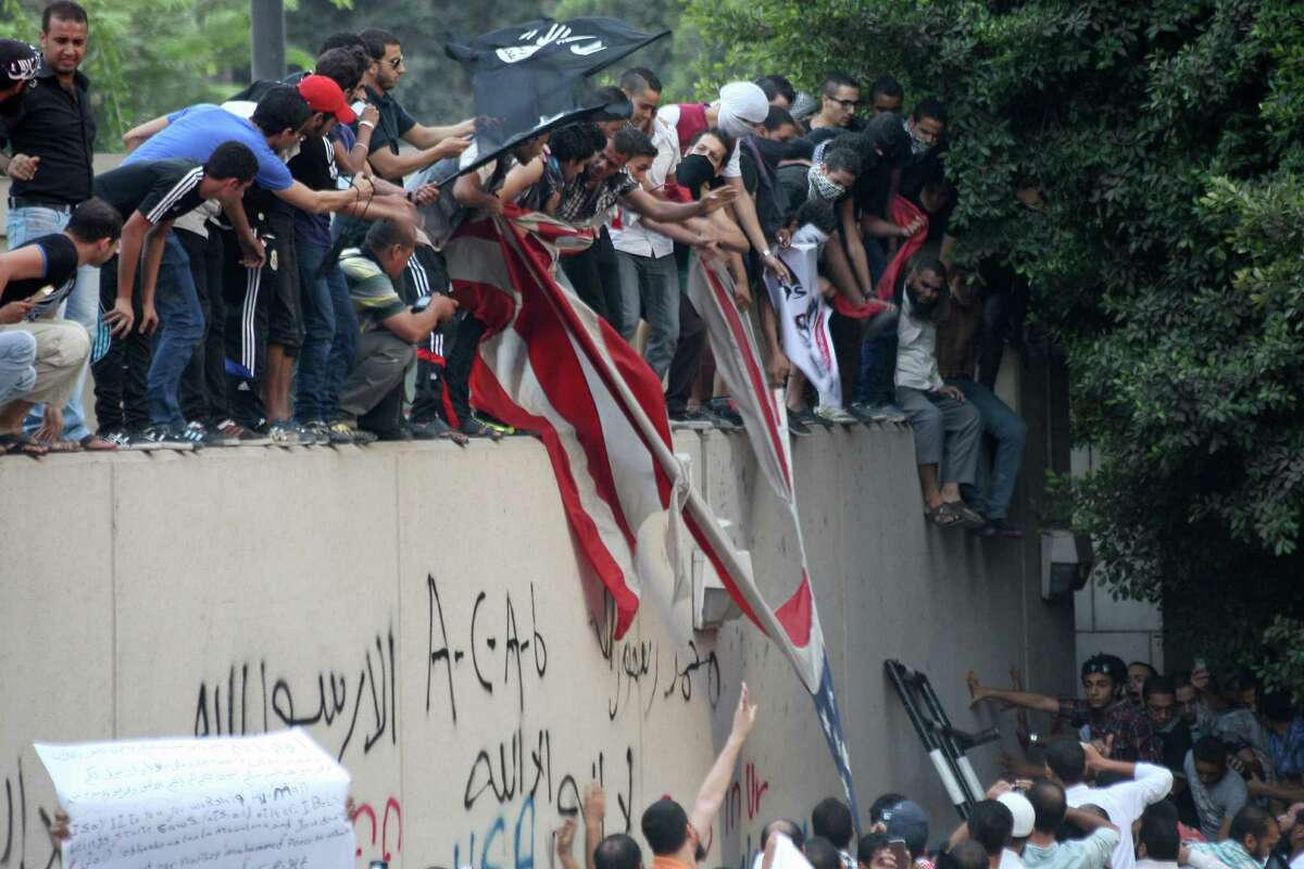 Protesters destroy an American flag pulled down from the U.S. embassy in Cairo om Tuesday. Egyptian protesters, largely ultra conservative Islamists, have climbed the walls of the U.S. embassy in Cairo, went into the courtyard and brought down the flag, replacing it with a black flag with Islamic inscription, in protest of a film deemed offensive of Islam. (AP Photo/Mohammed Abu Zaid)