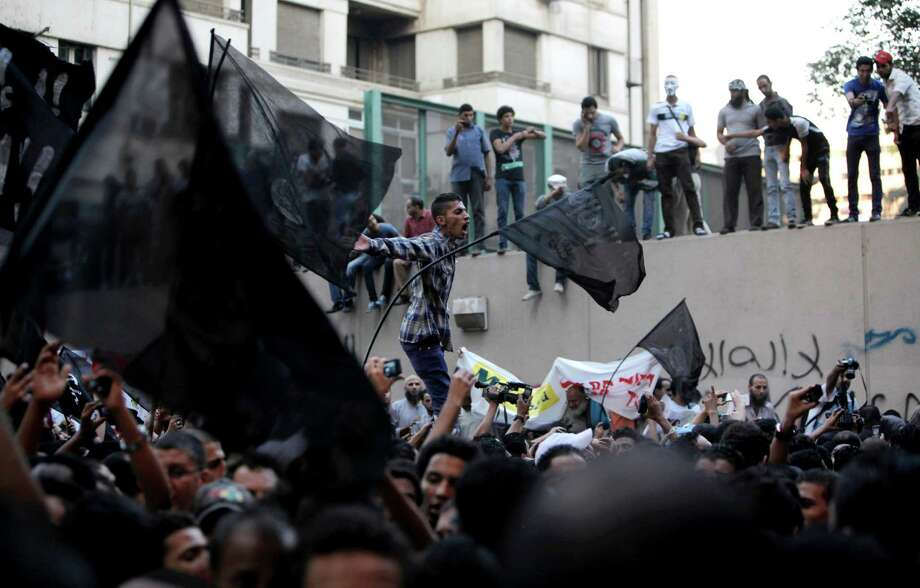 "Egyptian protesters climb the walls of the U.S. embassy while others chant anti U.S. slogans during a protest in Cairo Tuesday. Egyptian protesters, largely ultra conservative Islamists, have climbed the walls of the U.S. embassy in Cairo, went into the courtyard and brought down the flag, replacing it with a black flag with Islamic inscription, in protest of a film deemed offensive of Islam. Arabic graffiti reads ""Their is only one God."" (AP Photo/Nasser Nasser) Photo: Ap/getty"