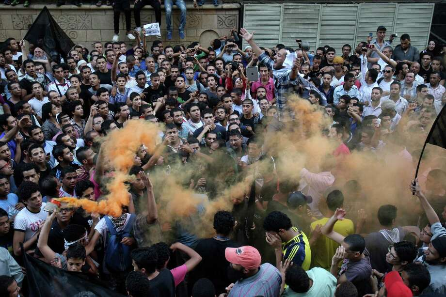 Protesters chant slogans amid orange smoke outside the U.S. embassy in Cairo on Tuesday. Egyptian protesters, largely ultra conservative Islamists, have climbed the walls of the U.S. embassy in Cairo, went into the courtyard and brought down the flag, replacing it with a black flag with Islamic inscription, in protest of a film deemed offensive of Islam. (AP Photo/Mohammed Abu Zaid) Photo: Ap/getty