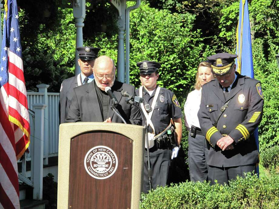 Msgr. Scheyde of St. Aloysius Church leads and invocation at the 9/11 memorial. Police Chief Nadriczny stands behind him, head bowed. Photo: Tyler Woods