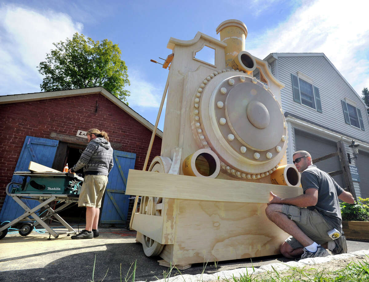 Thomas King, 37, of Redding , left, and Dan Land, 35, of Bethel, owner of Land Made, a custom carpentry business, work on a wooden train facade they were hired to build as a prop for a Broadway play, Tuesday, Sept. 11, 2012.