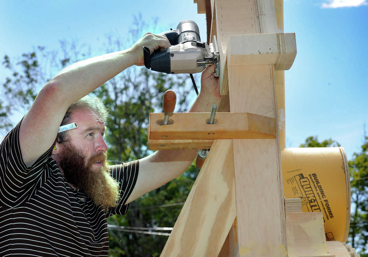 Thomas King, 37, of Redding, screws in a section of an engineer's window on a wooden train that is part of a set for a Broadway play, Tuesday, Sept. 11, 2012. King is working with Dan Land of Bethel to build the 7-feet-wide and almost 12-foot-tall structure .
