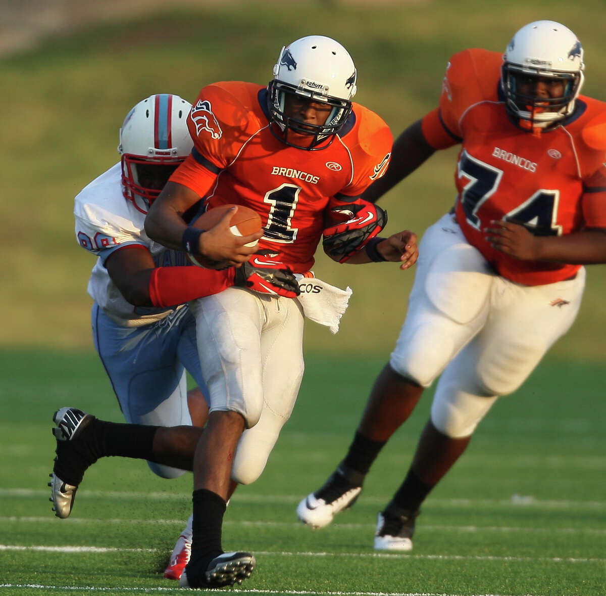 Bush quarterback Ronald Monroe (1) is tackled by Madison's Kerwin Green during the first half of a high school football game, Saturday, September 8, 2012, at Mercer Stadium in Sugar Land, TX.