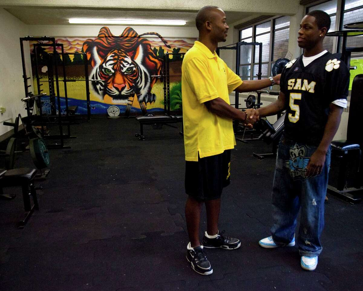 Head coach Rodney Dotson, left, greets Johnny Robinson, quarterback for Sam Houston High School, Wednesday, Nov. 12, 2008, in Houston. The Fightin' Tigers of Sam Houston High School hadn't won a game in five years when quarterback Johnny Robinson joined the team in August. But that didn't surprise him: a Hurricane Katrina evacuee, he knows the world can be harsh. And he wasn't surprised that his offensive line often left him unprotected. He's used to that, too. After relocating the family to Houston, his own mother moved back to New Orleans, leaving him and a teenage sister to fend for themselves. But this year, things have been turning around in Johnny's life, and people have been watching out for him. There's that sister, who supports him and her two little kids on a Target cashier's wages; there's his art teacher, who's e-mailing all her friends in search of an old computer that he can use; and there's his coach, who keeps an eye on Johnny's grades. Last week, Johnny's teammates joined that list -- and for the first time that anyone on the team could remember, the Tigers won a game. ( Karen Warren / Chronicle )