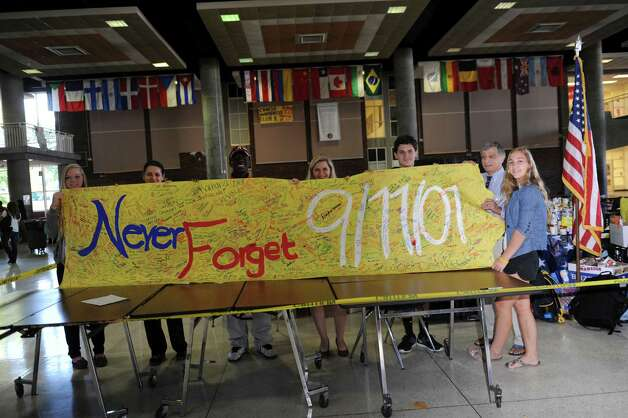 From left, Greenwich High School students Kelly Weigold, 16, Gardy LeBon, 16, Richard Alessi, Bella House administrator, and Matthew Pignataro, 16, stack food items to be donated to Neighbor-to-Neighbor Tuesday, Sept. 11, 2012. GHS Student Government and the Roots'N'Shoots Club had a day of service and remembrance by collecting food items for Greenwich-based Neighbor-to-Neighbor. Photo: Helen Neafsey / Greenwich Time