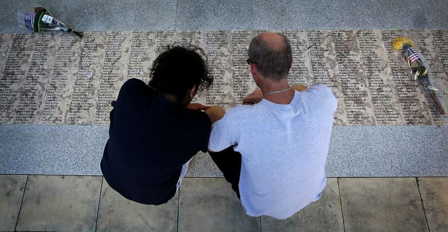 Glen McGuinness, right, retired from the NYPD, who was present at the attacks on the Twin Towers, kneels with a friend reading the names on the San Antonio 9/11 Memorial service held by New Life Christian Ministry,  Tuesday, Sept. 11, 2012. Photo: BOB OWEN, San Antonio Express-News / © 2012 San Antonio Express-News
