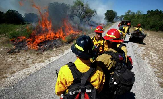 Firefighters from several agencies gather Tuesday, Sept. 11, 2012 along the fire line of a prescribed fire in Government Canyon State Park in western Bexar County as they examine how the fire is behaving before making their next move. More than 30 people were involved in the effort whch will continue Wednesday. Photo: William Luther, San Antonio Express-News / © 2012 San Antonio Express-News