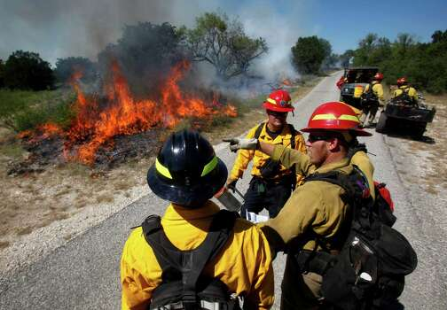 Firefighters from several agencies gather Tuesday, Sept. 11, 2012 along the fire line of a prescribed fire in Government Canyon State Park in western Bexar County as they examine how the fire is behaving before making their next move. More than 30 people were involved in the effort which will continue Wednesday. Photo: William Luther, San Antonio Express-News / © 2012 San Antonio Express-News