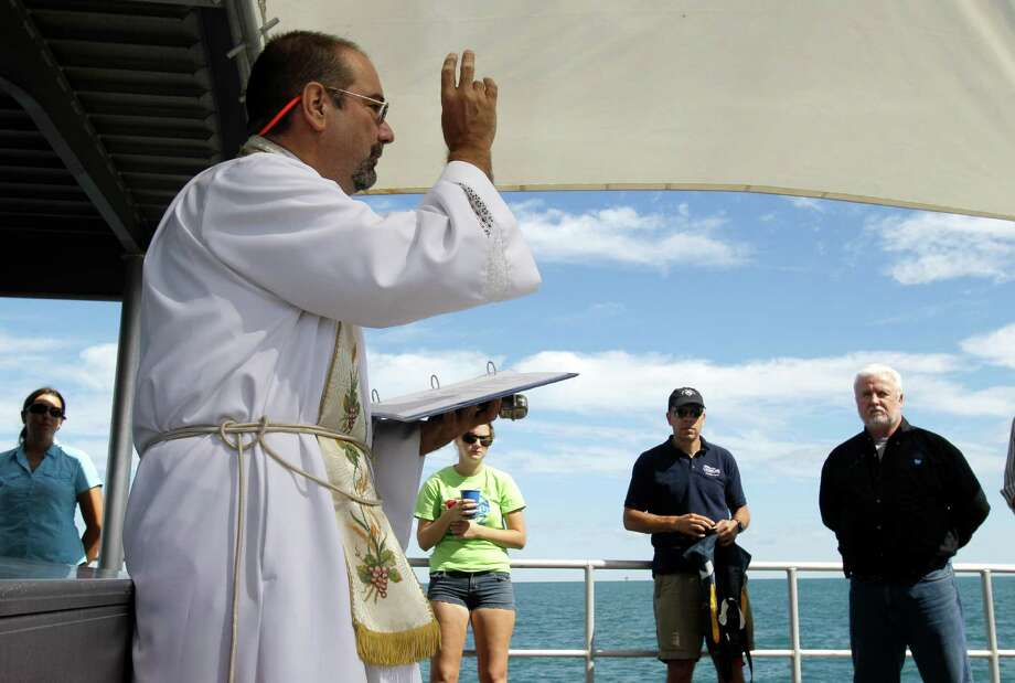 Aboard the RV Manta, Father Stephen Duncan, left, conducts a memorial service in the Gulf of Mexico off the Texas Coast Monday, Sept. 10, 2012, for the two men who died aboard the USS Hatteras in 1863 during the Civil War. The service was held at the site of the shipwreck where researchers are making a 3-D map using sonar equipment. (AP Photo/Pat Sullivan) Photo: Pat Sullivan, Associated Press / AP