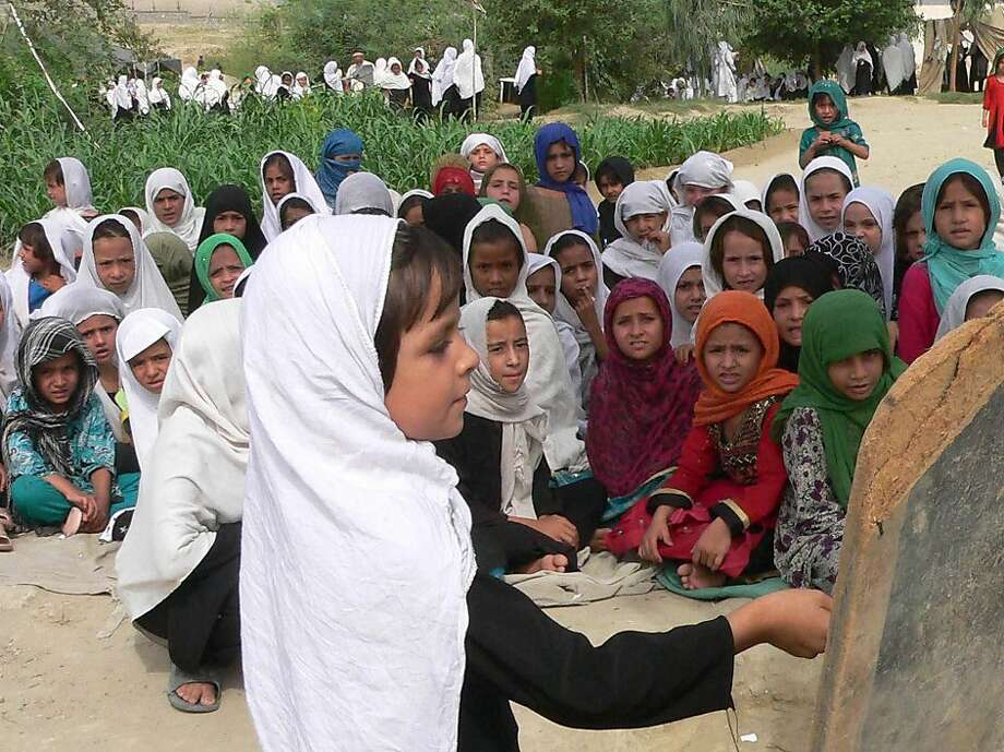 Girls are taught at an open-air school in Jalalabad on Sept. 11. Young Afghan women seeking an education are often targets of violence. Photo: Noorullah Shirzada, AFP/Getty Images
