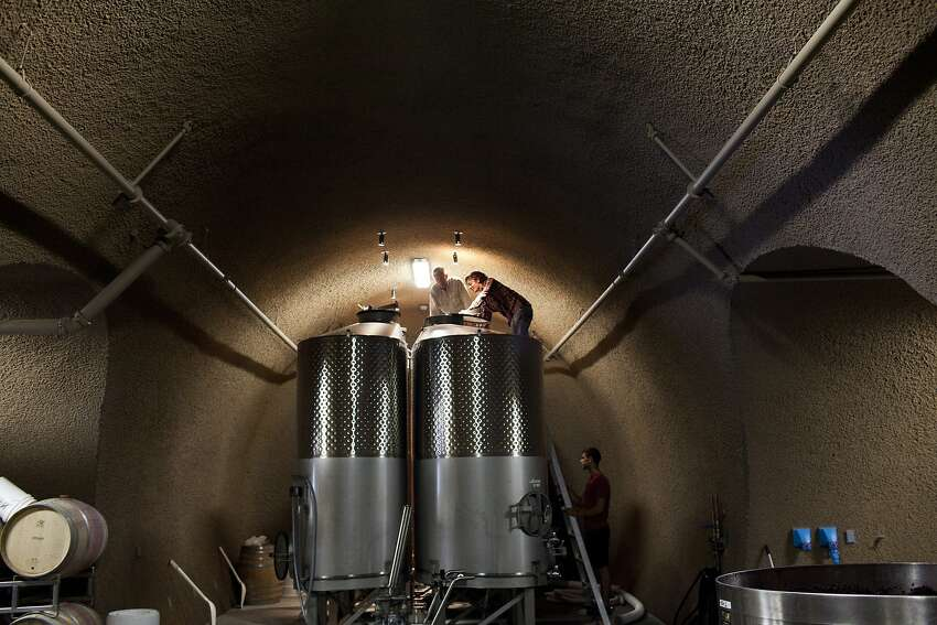 Greg Vita (center, above, and top) checkes fermenting Pinot Noir grapes at Holman Ranch.