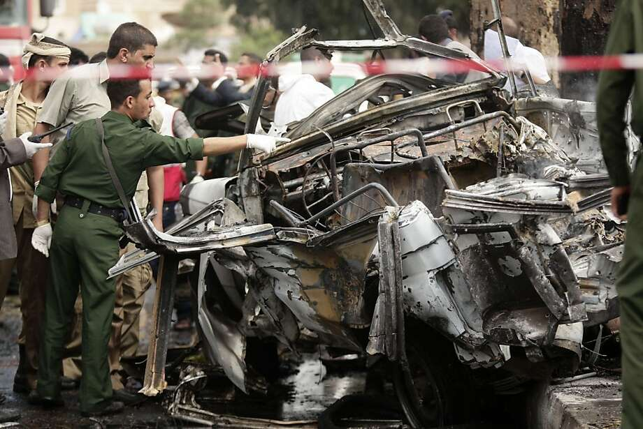 Forensic police officers collect evidence at the site of a car bomb attack targeting the motorcade of Yemen's defense minister in Sanaa. He was in a previous vehicle and escaped unhurt. Photo: Hani Mohammed, Associated Press