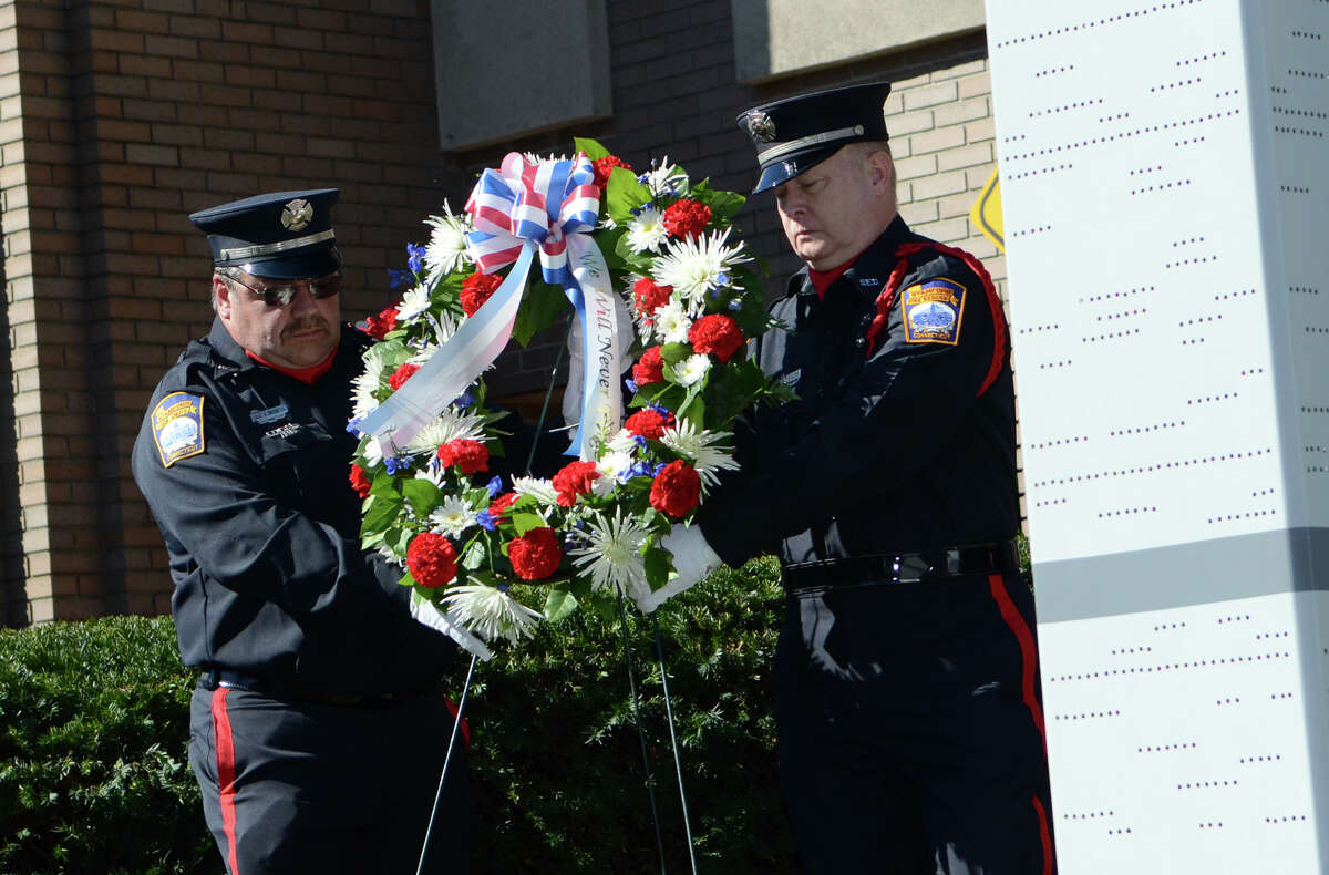 Firefighter Dave Bocchetta, Engine 2, and retired firefighter Ricky Gillespie, place a wreath near the 9/11 Twin Towers memorial during the Stamford Fire & Rescue Department (SFR) and the Stamford Professional Fire Fighters Association 9/11 Memorial Observance in front of Station 5 on Washington Blvd. in Stamford on Tuesday, Sept. 11, 2012.