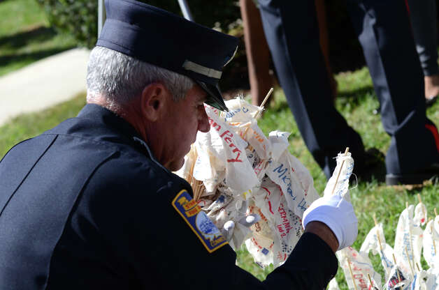 Bill Avalos, retired Captain of the Stamford Fire Department, holds flags bearing the names of the 343 fallen fire fighters during the Stamford Fire & Rescue Department (SFR) and the Stamford Professional Fire Fighters Association 9/11 Memorial Observance in front of Station 5 on Washington Blvd. in Stamford on Tuesday, Sept. 11, 2012. Photo: Amy Mortensen / Connecticut Post Freelance