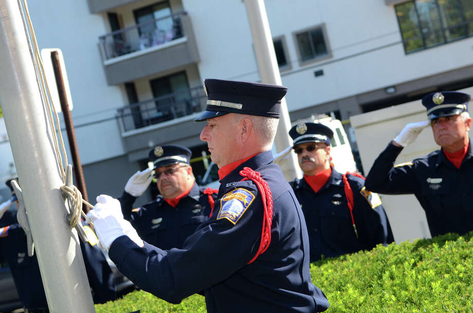 Fire Captain Mark Shannon lowers the flag to half staff during the Stamford Fire & Rescue Department (SFR) and the Stamford Professional Fire Fighters Association 9/11 Memorial Observance in front of Station 5 on Washington Blvd. in Stamford on Tuesday, Sept. 11, 2012. Photo: Amy Mortensen / Connecticut Post Freelance