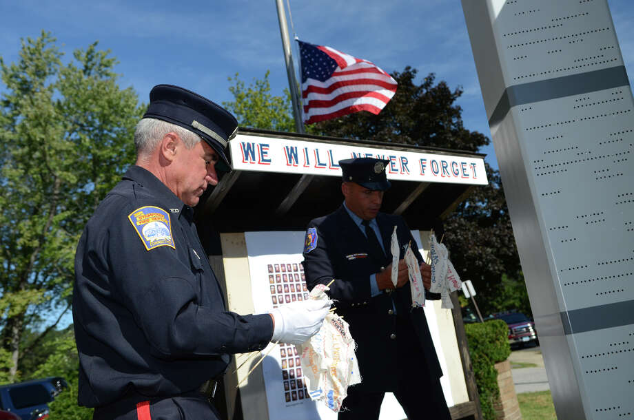 Bill Avalos, retired Stamford Fire Captain, and Stamford firefighter Michael Dragonetti, hold flags bearing the names of the 343 firefighters lost on 9/11 during the Stamford Fire & Rescue Department (SFR) and the Stamford Professional Fire Fighters Association 9/11 Memorial Observance in front of Station 5 on Washington Blvd. in Stamford on Tuesday, Sept. 11, 2012. Photo: Amy Mortensen / Connecticut Post Freelance