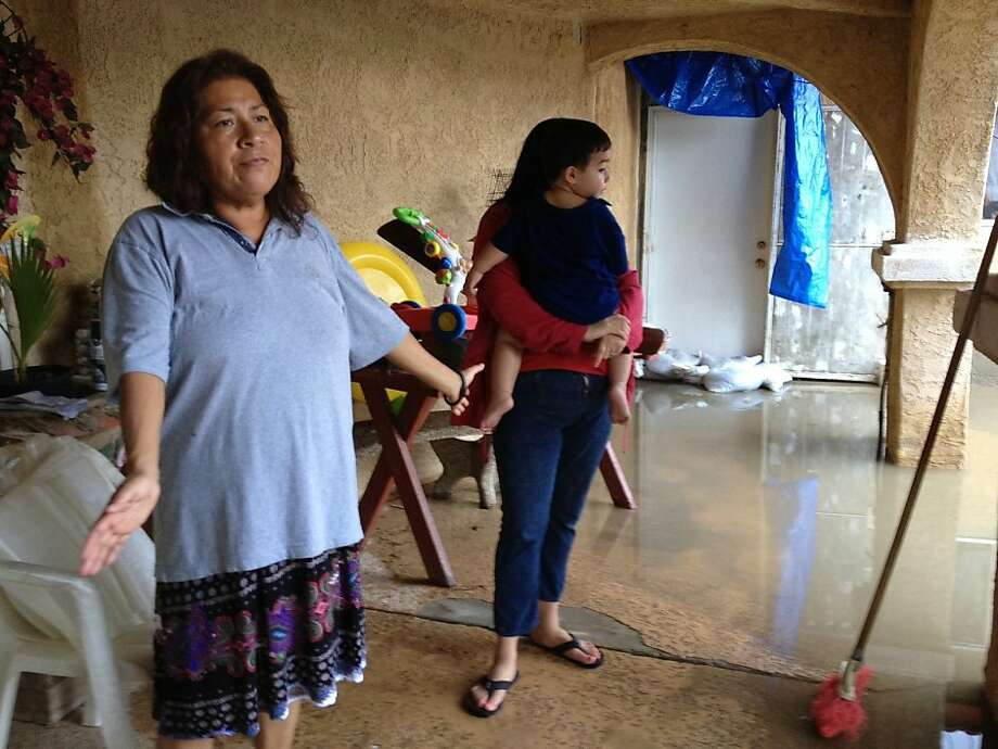 Martha Manangan (left) surveys her flooded home in Mecca (Riverside County), which got more than 5 1/2 inches of rain in an overnight thunderstorm. Photo: Denise Goolsby, Associated Press