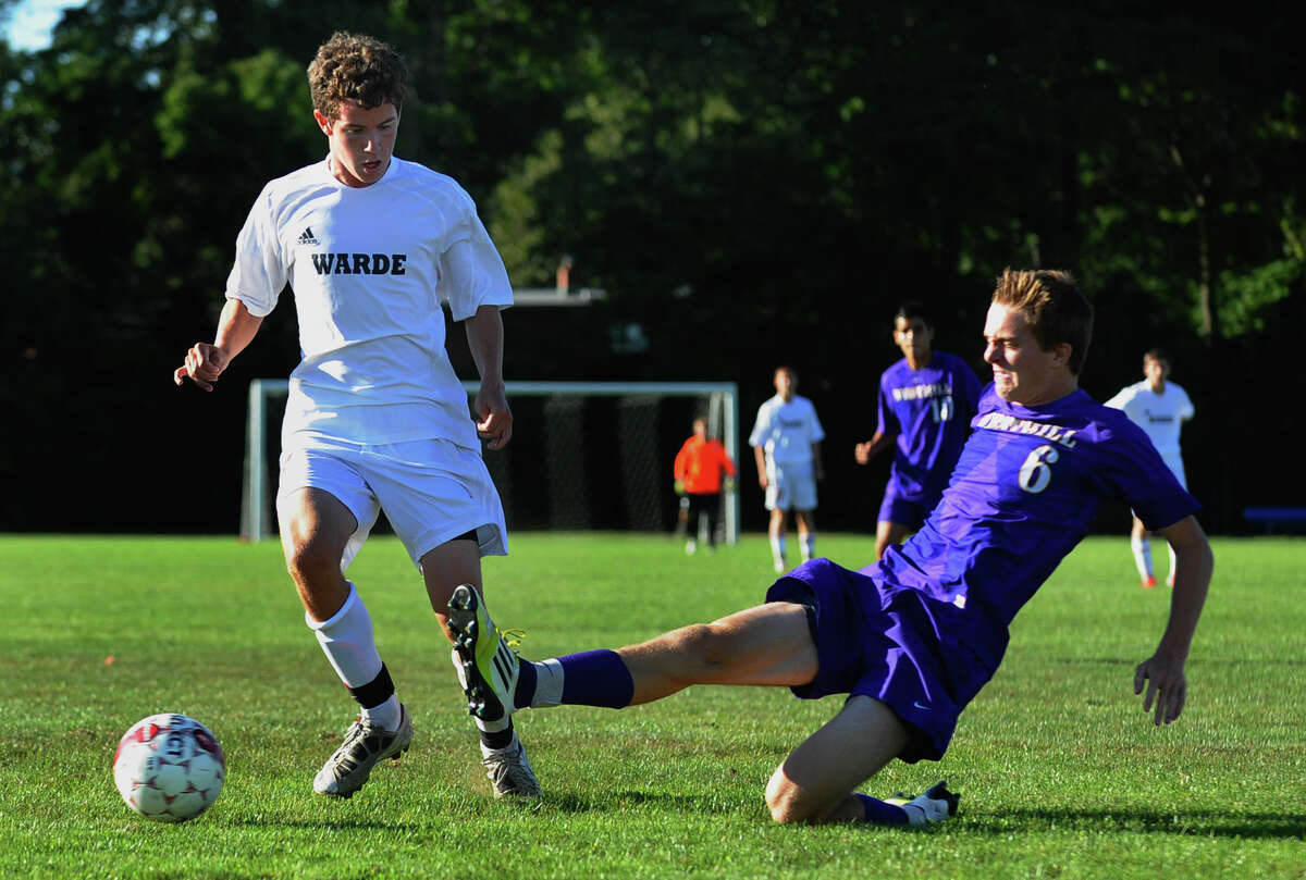 Westhill's #6 Sam Jelliffe, right, kicks the ball away from Fairfield Warde's #7 Stuart Peters, during boys soccer action in Fairfield, Conn. on Tuesday September 11, 2012.