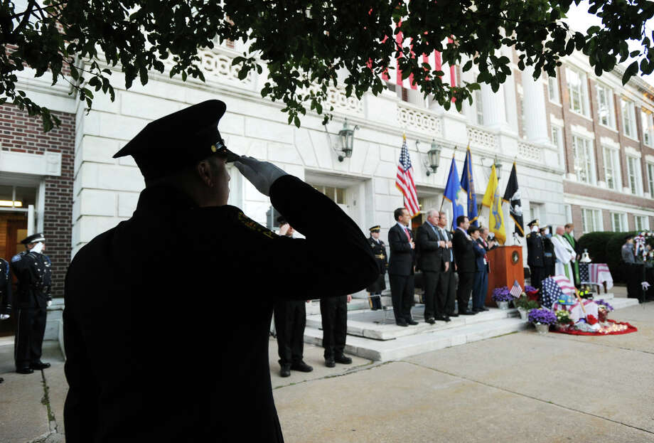 Greenwich Police Officer Andres Sanchez salutes during the conclusion of the 9/11 remembrance ceremony at Greenwich Town Hall, Tuesday night, Sept. 11, 2012. Photo: Bob Luckey / Greenwich Time