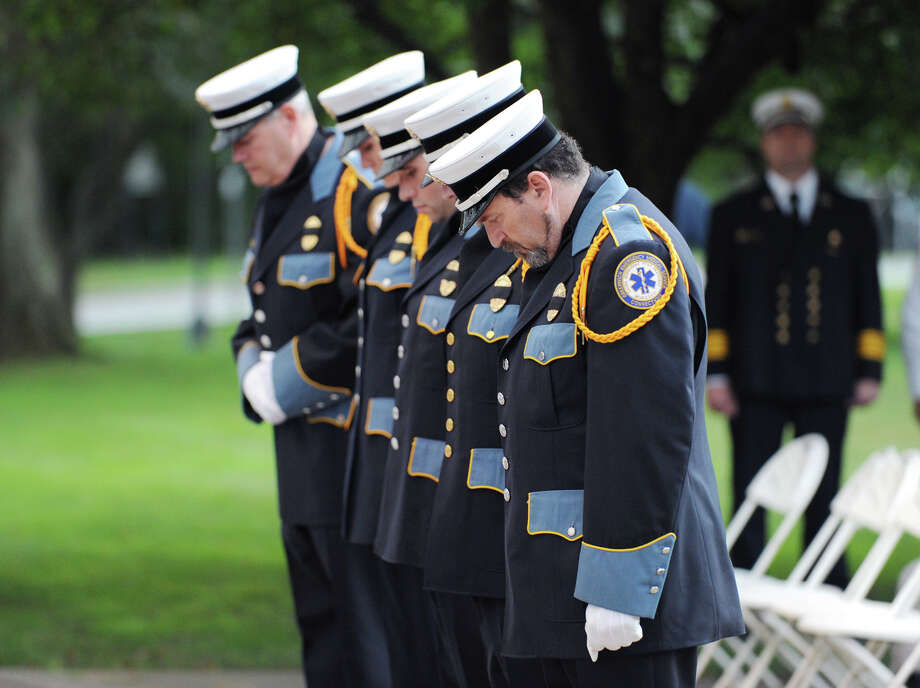 Walter Hughes, right, of the Greenwich Emergency Medical Services, and colleagues, bow their heads during the 9/11 remembrance ceremony at Greenwich Town Hall, Tuesday night, Sept. 11, 2012. Photo: Bob Luckey / Greenwich Time