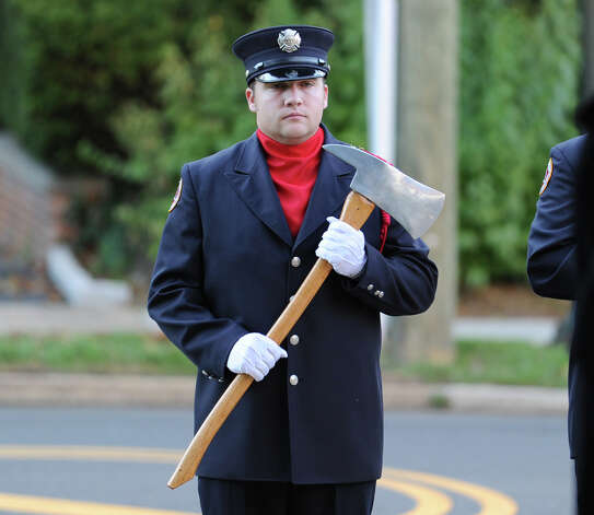 Greenwich Firefighter Daniel Byrne holds a fireman's ax during the 9/11 remembrance ceremony at Greenwich Town Hall, Tuesday night, Sept. 11, 2012. Photo: Bob Luckey / Greenwich Time