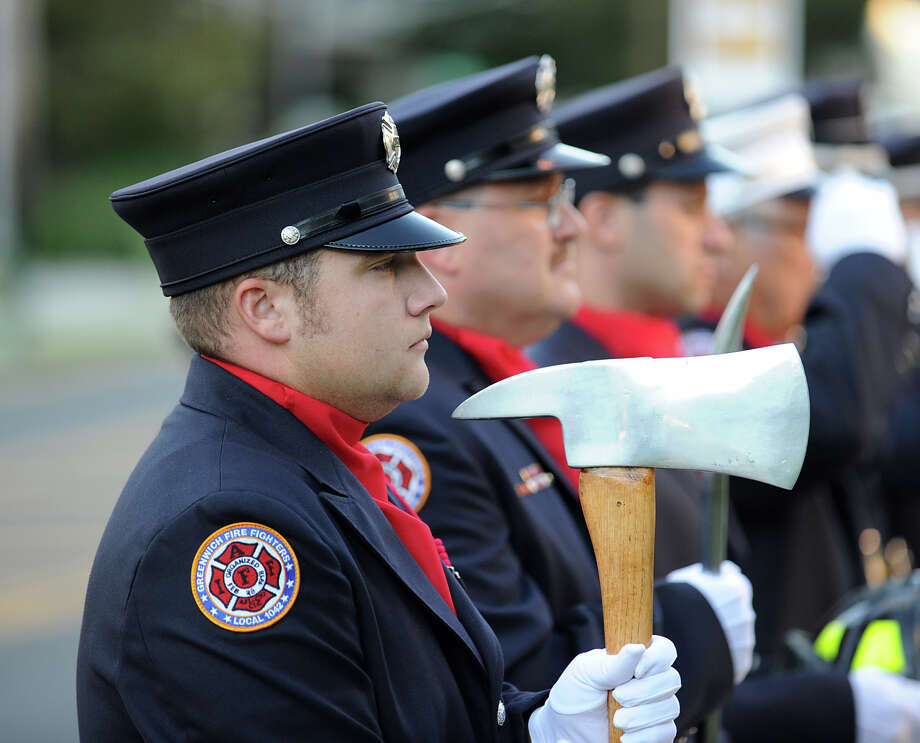 Daniel Byrne of the Greenwich Fire Department with a fireman's ax during the 9/11 remembrance ceremony at Greenwich Town Hall, Tuesday night, Sept. 11, 2012. Photo: Bob Luckey / Greenwich Time