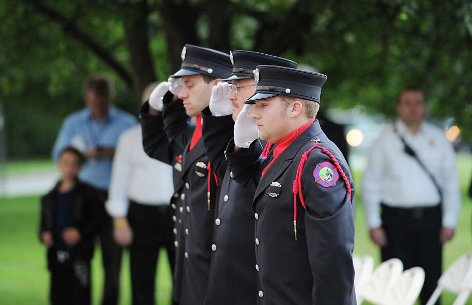 Greenwich Firefighters salute during the 9/11 remembrance ceremony at Greenwich Town Hall, Tuesday night, Sept. 11, 2012. Photo: Bob Luckey / Greenwich Time