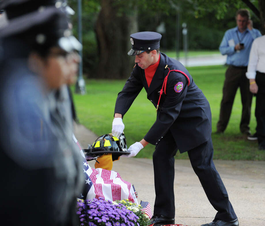Greenwich Firefighter Matt Gordiski places a fireman's helmet during the 9/11 remembrance ceremony at Greenwich Town Hall, Tuesday night, Sept. 11, 2012. Photo: Bob Luckey / Greenwich Time