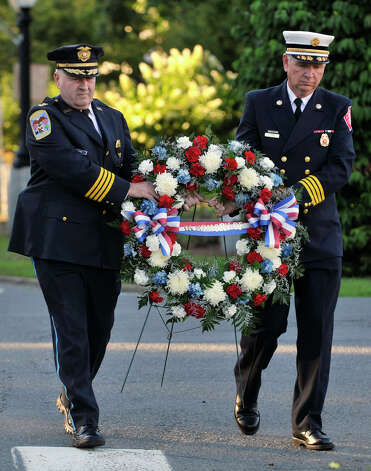 Police Chief Alan Baker, left, and Deputy Fire Chief T.J. Wiedl carry a wreath during the 9/11 memorial ceremony at Elmwood Park in Danbury on Sept. 11, 2012. Photo: Jason Rearick / The News-Times