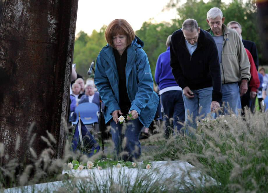 Lori Seibert, of Ridgefield, places a rose at the foot of monument at the close of Ridgefield's 9/11 memorial ceremony Tuesday, Sept. 11, 2012. Photo: Carol Kaliff / The News-Times