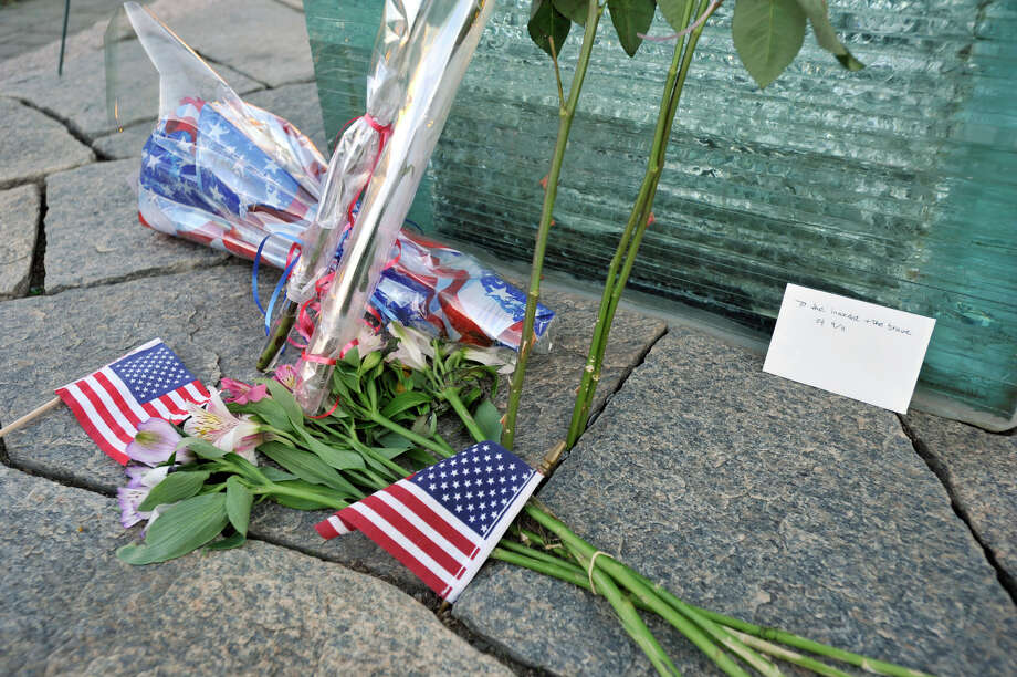 "Flowers, flags and a small envelope with the words ""To the innocent + the brave of 9/11"" sit at the base of the glass memorial after the 9/11 ceremony at Elmwood Park in Danbury on Sept. 11, 2012. Photo: Jason Rearick / The News-Times"
