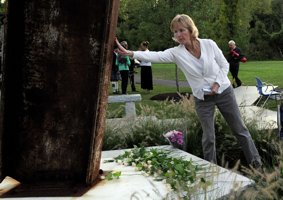 A woman touches the 9/11 memorial after placing a flower at the foot of it at the close of Ridgefield's Sept. 11 memorial ceremony Tuesday, Sept. 11, 2012. Photo: Carol Kaliff / The News-Times